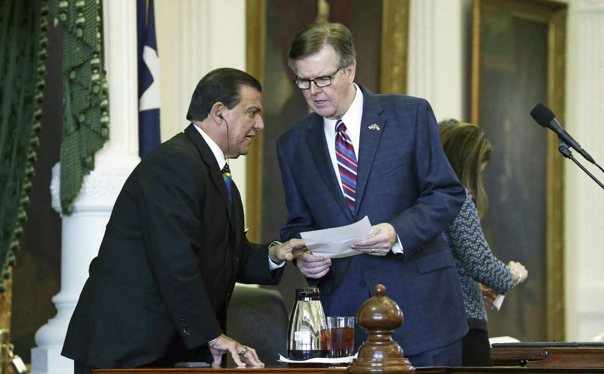 Senator Eddie Lucio gives some paperwork to Lt. Governor Dan Patrick as the so called bathroom bill is about to be presented on the floor of the Senate in the State Capitol on March 14, 2017.