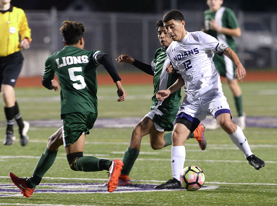 Port Neches - Groves' Christian Davalos maneuvers to keep the ball away from Livingston's defenders during their match-up at Port Neches Tuesday. The game marked the end of regular season play for the Indians, who took the field undefeated in District 22 - 5A. Photo taken Tuesday, March 14, 2017 Kim Brent/The Enterprise Photo: Kim Brent / BEN