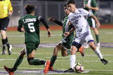 Port Neches - Groves' Christian Davalos maneuvers to keep the ball away from Livingston's defenders during their match-up at Port Neches Tuesday. The game marked the end of regular season play for the Indians, who took the field undefeated in District 22 - 5A. Photo taken Tuesday, March 14, 2017 Kim Brent/The Enterprise