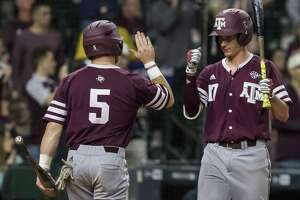 Texas A&M's Logan Foster (5) and Joel Davis celebrate after Foster scored against Baylor at Minute Maid Park in March 5, 2017, in Houston.