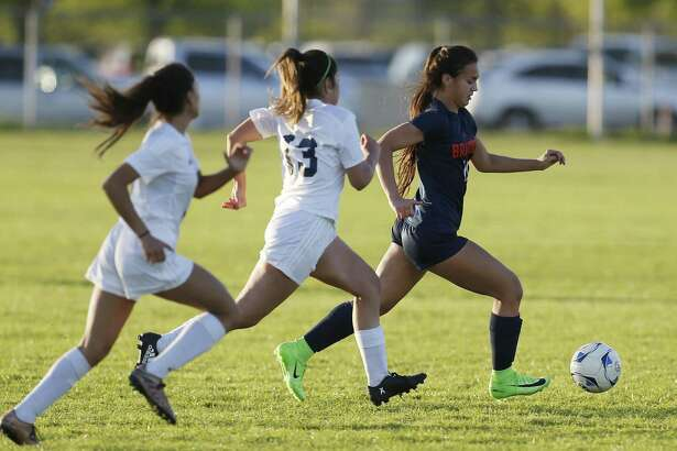 Brandeis' Samantha Palomino (right) pushes ahead of two Jay defenders in girls soccer at Northside Athletic Complex on March 14, 2017.