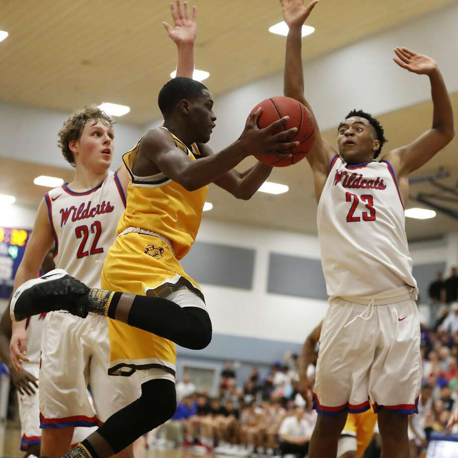 Tyrese Johnson (4) of Mission High School passes the ball as he is being defended by Brandon Beckman (22) and Wrenn Robinson (23) of St. Ignatius College Preparatory during the fourth quarter of their CIF Division III Basketball regional semifinal at McCullough Gymnasium in San Francisco, Calif. on Tuesday, Mar. 14, 2017. Photo: Stephen Lam, Special To The Chronicle