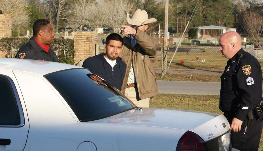 Roberto Ismael Alvarado is shown being taken out of a squad car and into Cleveland Police Department just days after the Dec. 16, 2015, robbery and shooting death of Conbino Crasto, a store clerk at the Exxon station on FM 2025 near Baldwin Park. Photo: File Photo