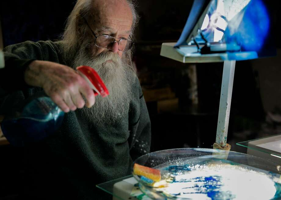 Bill Ham, above, adds Windex to paint while demonstrating his swirling light projection paintings. Photo: Gabrielle Lurie, The Chronicle