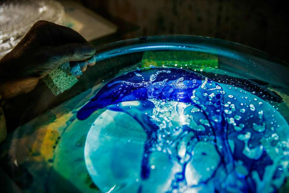 Bill Ham moves paint around on a plate while demonstrating his light projection paintings at his studio. Photo: Gabrielle Lurie, The Chronicle