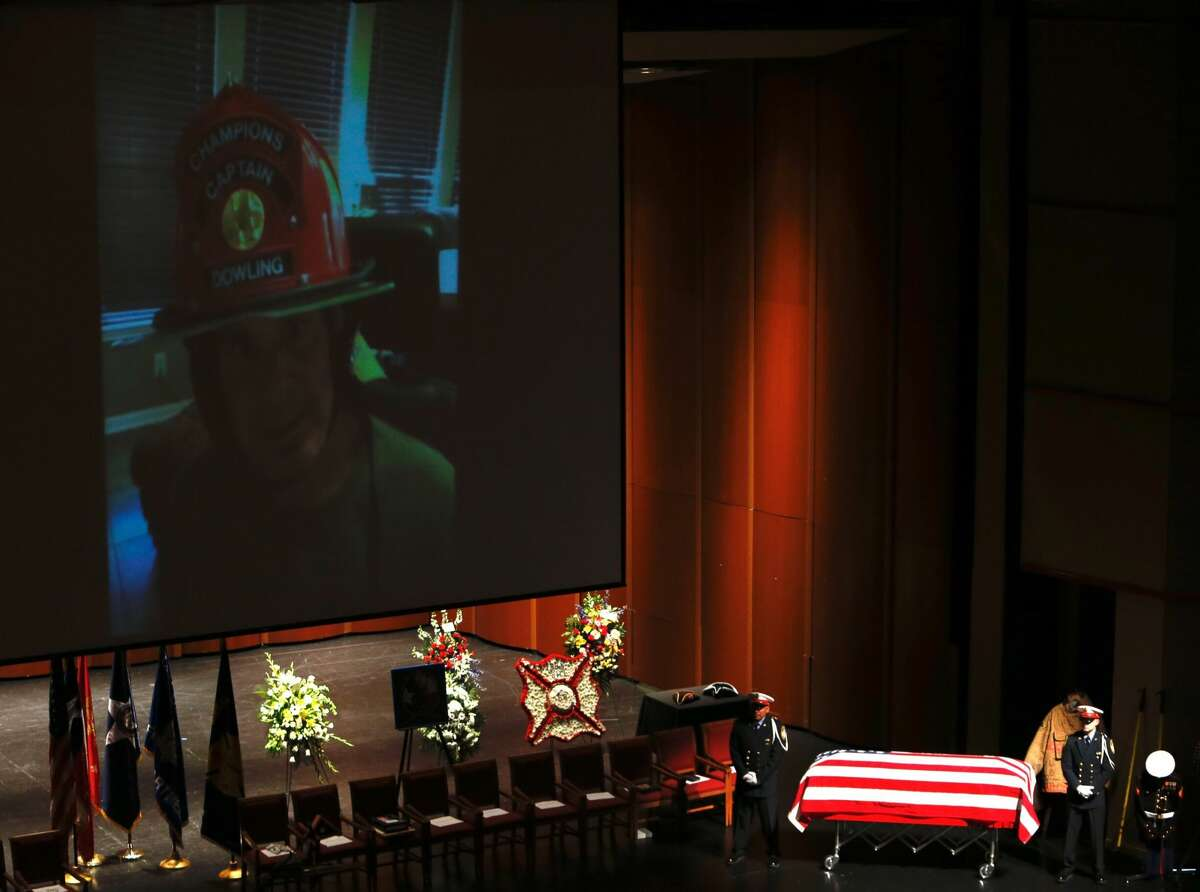 An honor guard stands at attention by the casket of Houston Fire Capt. William