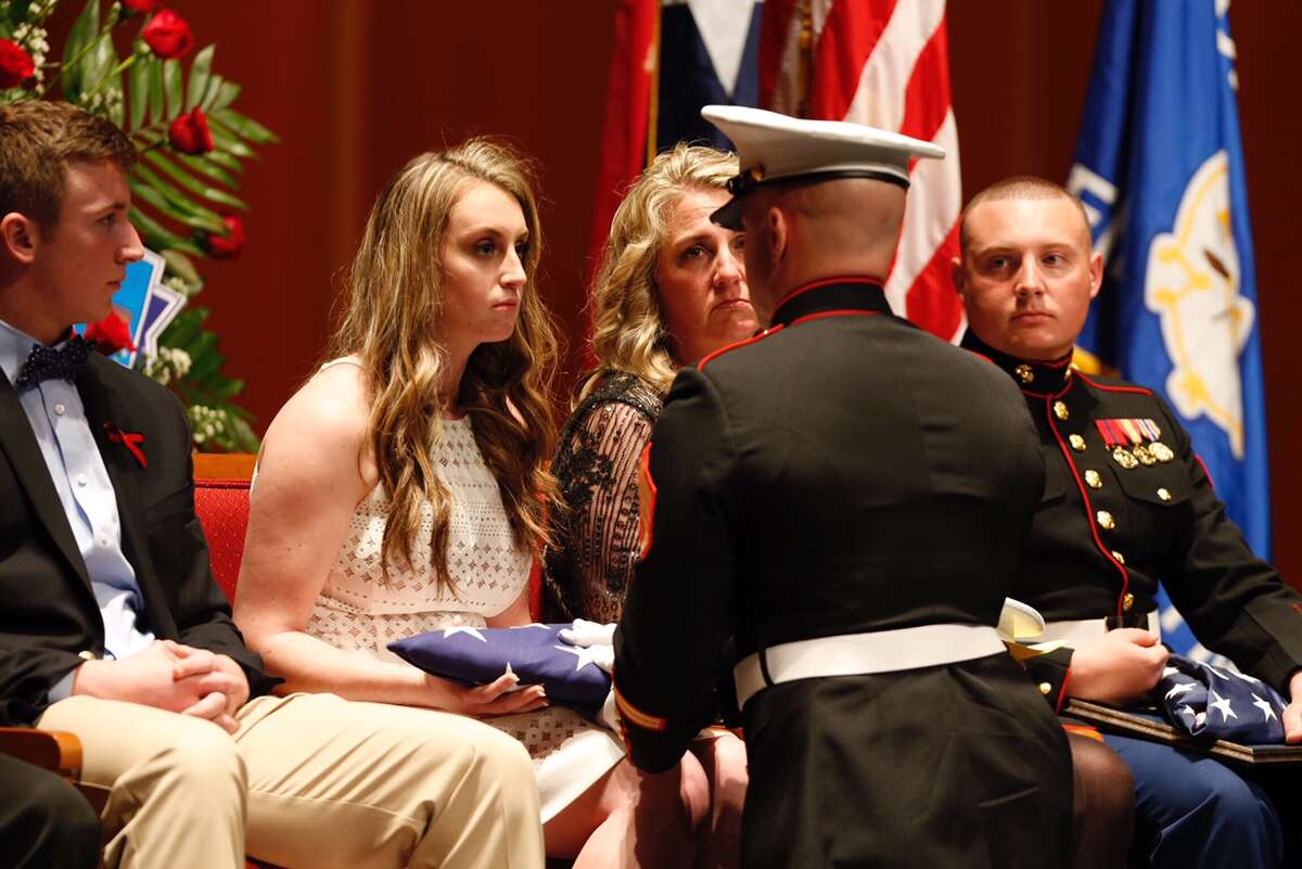 Faith Dowling is presented an American flag by a Marine Honor Guard during the memorial for her father, Houston Fire Capt. William