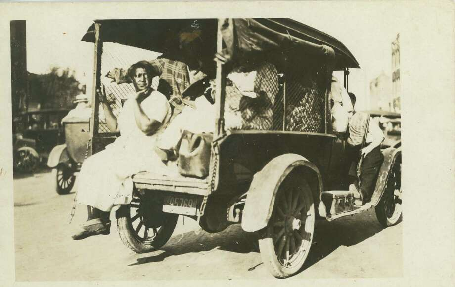 Photograph of African Americans taken prisoner during the Tulsa Race Riot, 1921. The photo shows a small truck loaded with people. A woman sits with her legs dangling from the back of the truck. An armed white man rides on the running board of the automobile. (Courtesy of Tulsa Historical Society & Museum)