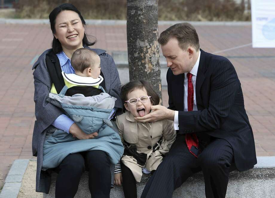 Robert Kelly and Jung-a Kim wait for a press conference to begin with their children in Busan, South Korea, following Kelly's much-watched BBC interview. Photo: Ha Kyung-min, Associated Press