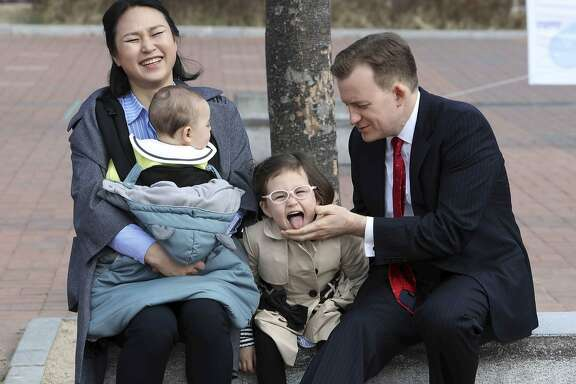 "Robert Kelly, right, a political science professor at Pusan National University, waits for a press conference with his wife Jung-a Kim, left, and children James and Marion, at the university in Busan, South Korea, Wednesday, March 15, 2017. As Kelly speaks from his home office via Skype with BBC about the just-ousted South Korean president, his eyes dart left as he watches on his computer screen as his young daughter parades into the room behind him. Her jaunty entrance resembles the exuberant march of the Munchkins celebrating the Wicked Witch's death in the ""The Wizard of Oz."" (Ha Kyung-min/Newsis via AP)"