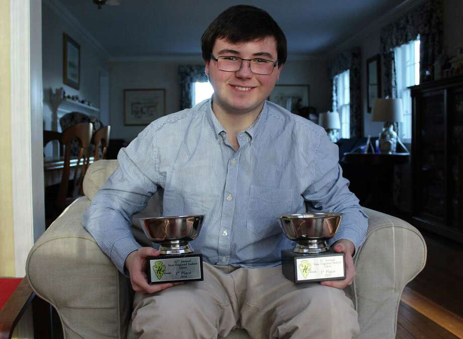Henry Keena poses with two of his trophies at his home in Darien. Photo: Erin Kayata / Hearst Connecticut Media / Darien News