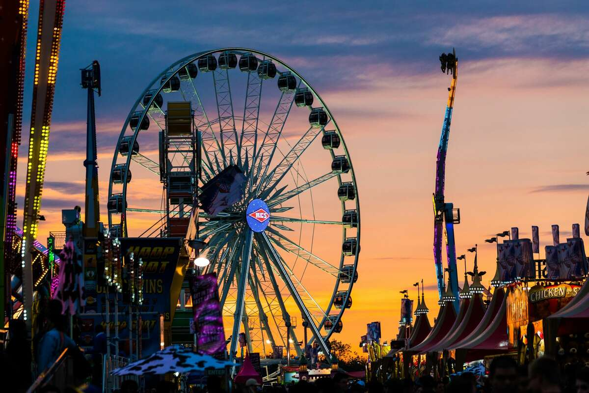 The sun sets at NRG park as the RodeoHouston 2017 carnival lights begin to shine in the night.