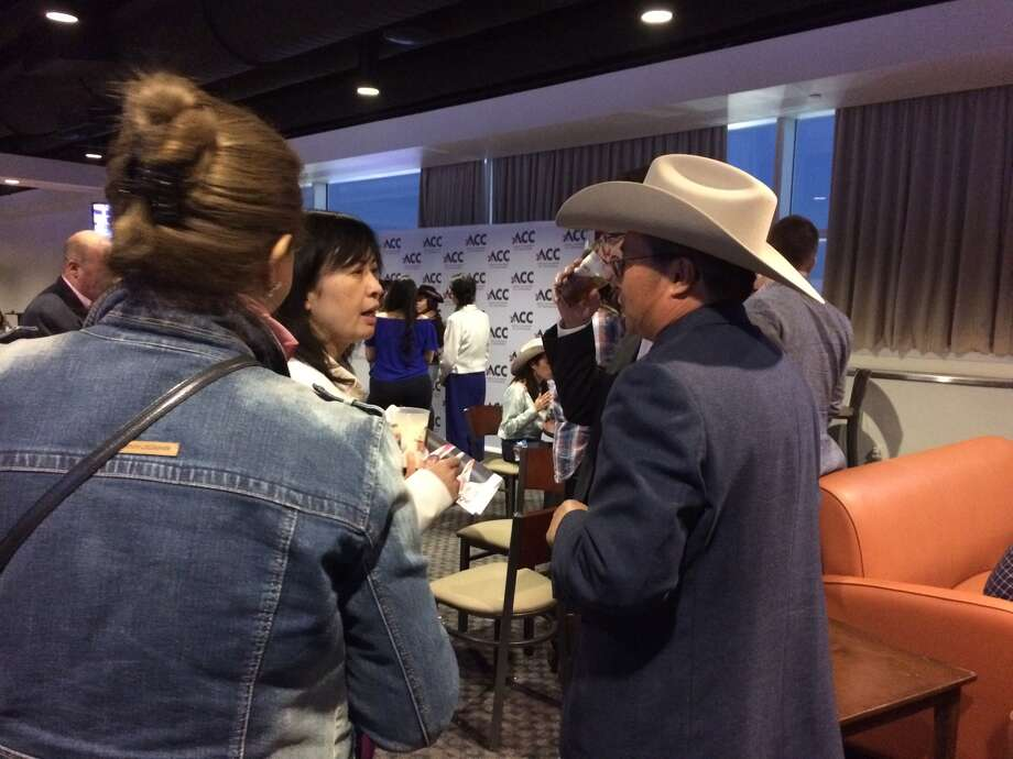 Austin Zhao (right), chair of the Asian Chamber of Commerce board, speaks with attendees at Asian Night at the Rodeo.