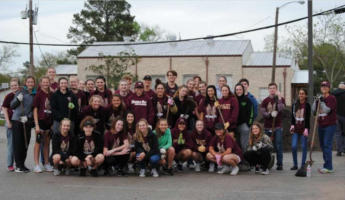 Magnolia West softball, volleyball and National Honor Society students working at the Magnolia library.