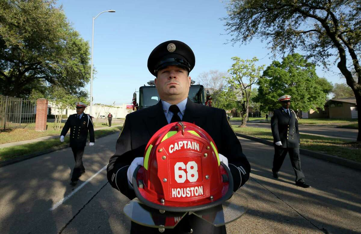Justin Miller, with Houston Fire Station 68, carries a captain's helmet from during the procession that lead to the memorial service for fallen Houston Fire Capt. William
