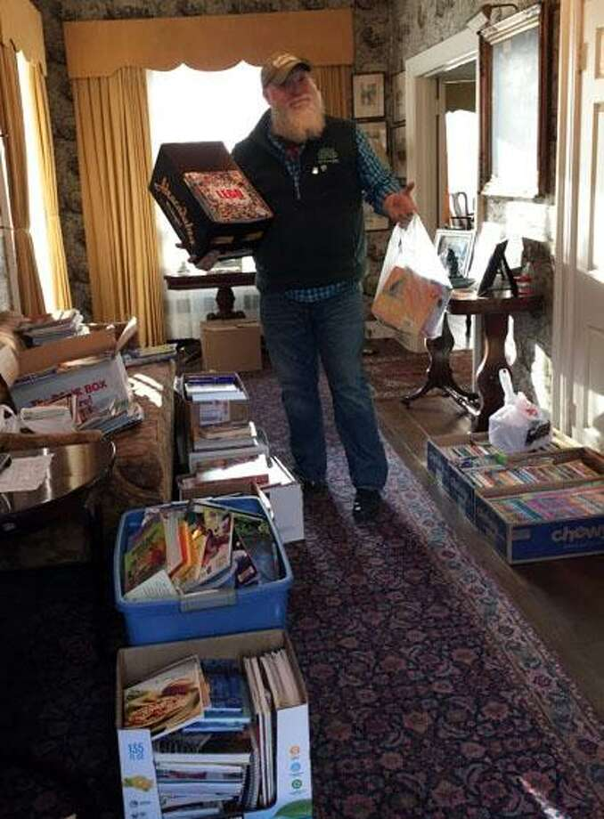 Billy Buckbee, executive director of Harrybrooke, proudly shows off some of the boxes of books dropped off by local residents for the book drive. Photo: Contributed Photo / The News-Times Contributed