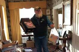 Billy Buckbee, executive director of Harrybrooke, proudly shows off some of the boxes of books dropped off by local residents for the book drive.