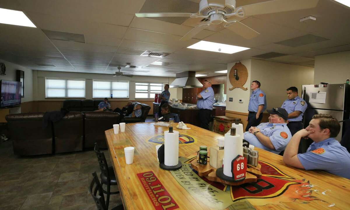 Sugar Land firefighters and Houston Fire volunteers watch the live broadcast of the memorial service for Houston Fire Capt. William