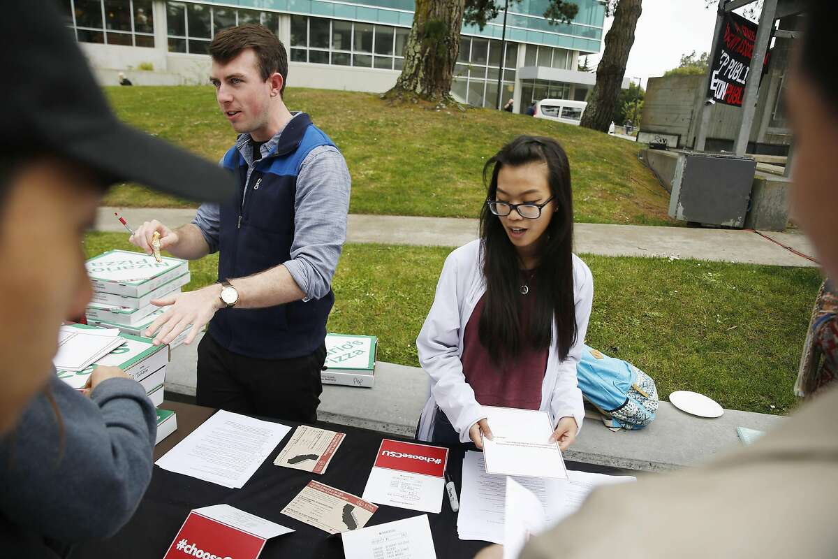 Michael Overby (l to r), Associated Students vice president of Finance and Ivy Tran, Associated Students freshman representative, talk to students as they hand out information during an anti tuition increase demonstration at San Francisco State University on Wednesday, March 15, 2017 in San Francisco, Calif.