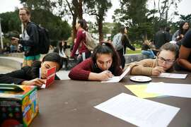 Ashley Sarkodie, graduate of CSU Fullerton; Alejandra Mendez-Ruiz, SFSU student and Jordan Zabek, SFSU student, fill out cards during an anti tuition increase demonstration at San Francisco State University on Wednesday, March 15, 2017 in San Francisco, Calif.