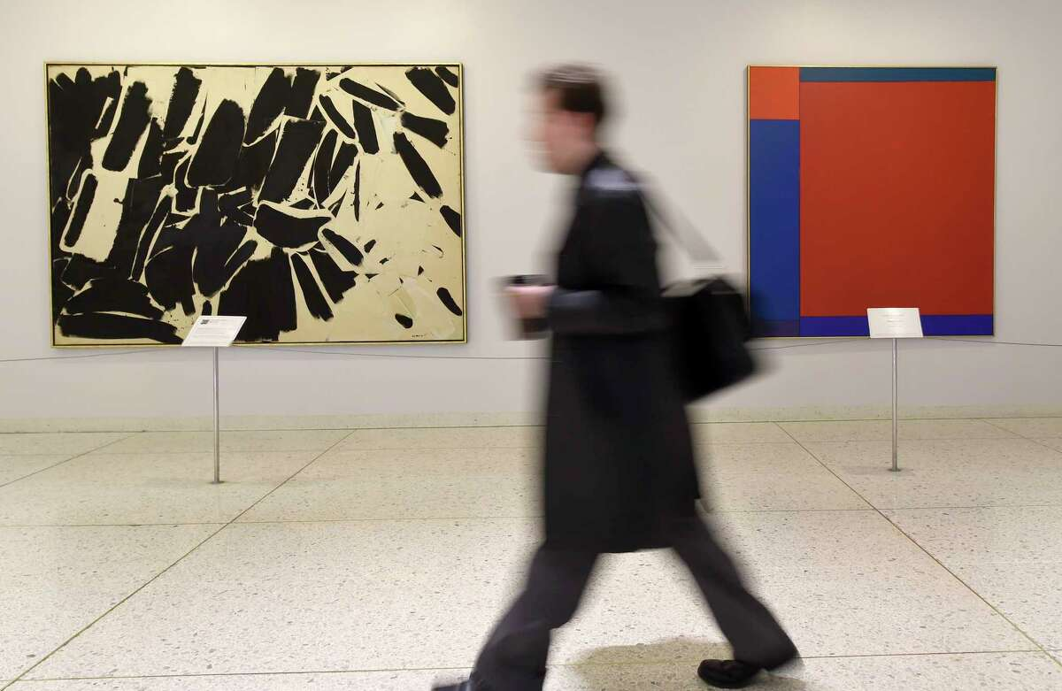 FILE - A person walks past the artwork of the Governor Nelson A. Rockefeller Empire State Plaza Art Collection and is on display during the 50th anniversary of the collection which adorns the walls of the Concourse of the Empire Plaza Feb. 2, 2016 in Albany, N.Y. (Skip Dickstein/Times Union)