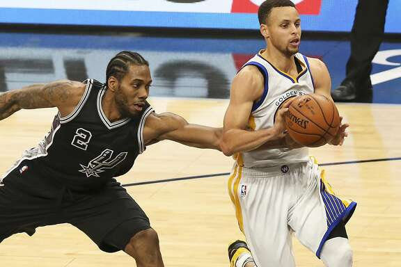 Kawhi Leonard tries to make a steal on Stephen Curry as the Spurs host Golden State at the AT&T Center on April 10, 2016.