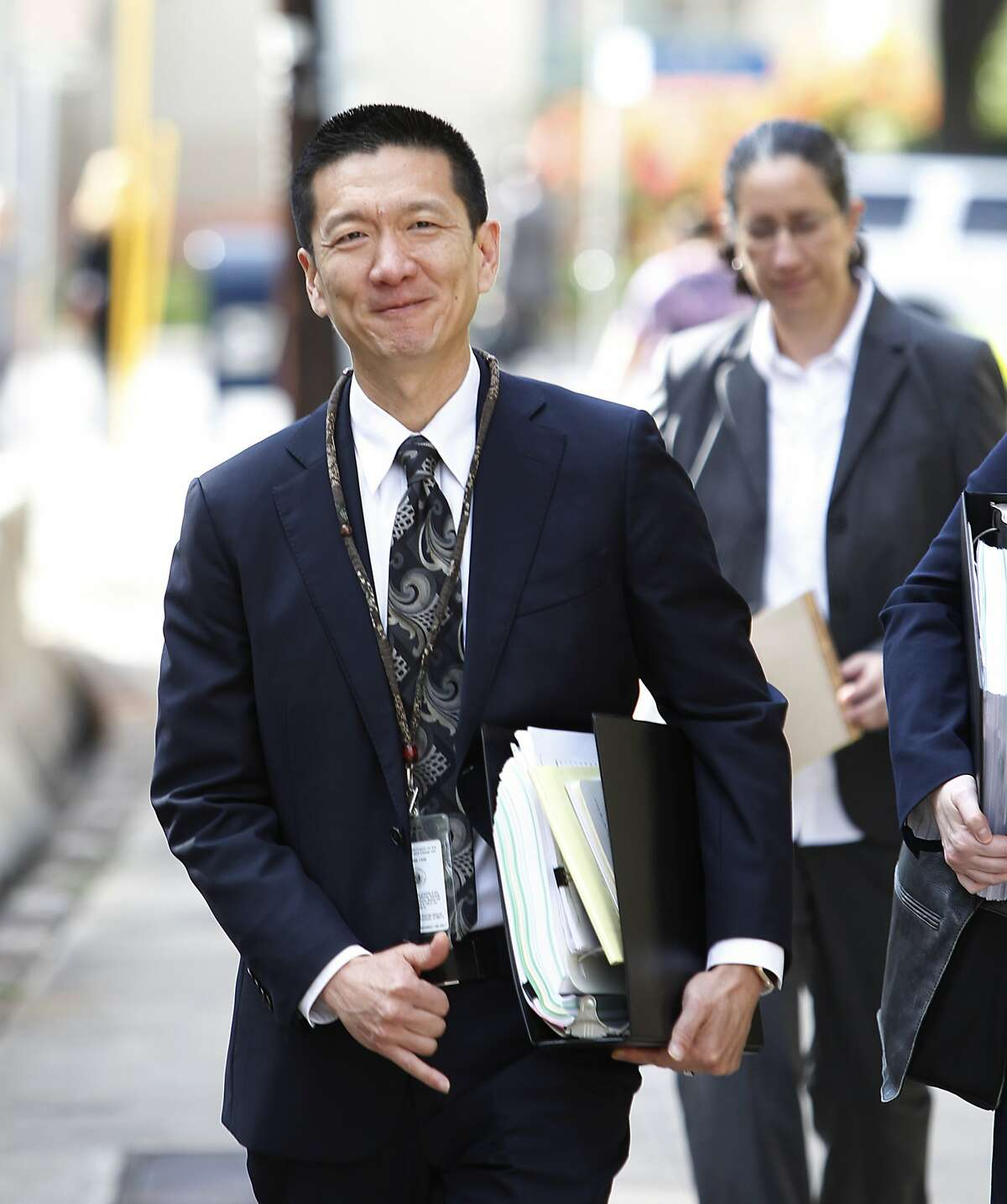 Hawaii Attorney General Douglas Chin flashes a Hawaii shaka before entering federal court, Wednesday, March 15, 2107, in Honolulu. Legal efforts to overturn President Donald Trump's travel ban will be held Wednesday in Hawaii. The lawsuit claims the ban harms Hawaii by highlighting the state's dependence on international travelers, its ethnic diversity and its welcoming reputation as the Aloha State. (AP Photo/Marco Garcia)