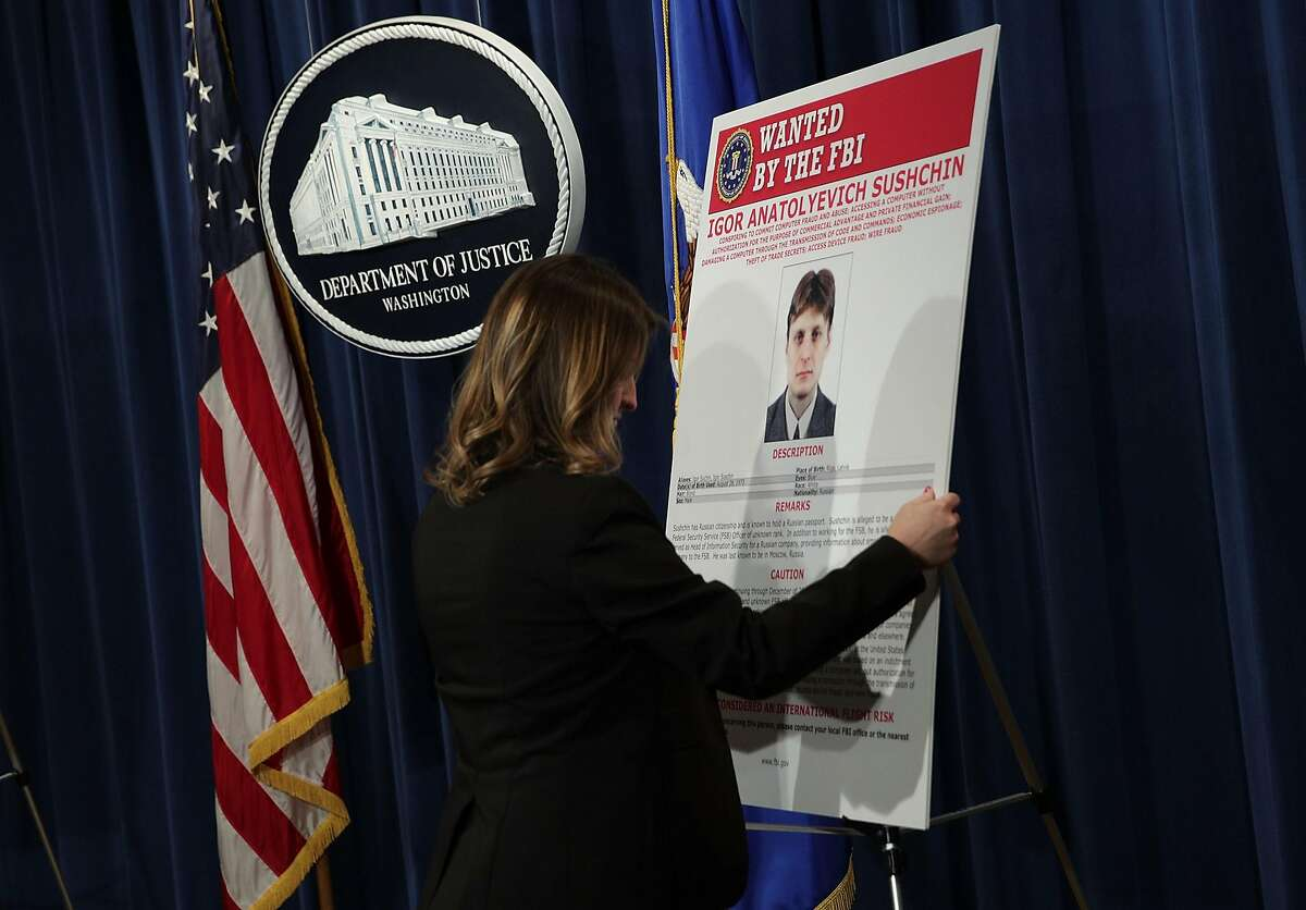 WASHINGTON, DC - MARCH 15: A U.S. Justice Department employee put up a wanted poster of Igor Anatolyevich Sushchin, A Russian national and resident, prior to a news conference at the Justice Department March 15, 2017 in Washington, DC. A grand jury in the Northern District of California has indicted four defendants, including two officers of the Russian Federal Security Service (FSB), for hacking into Yahoo�s network system and stealing information from about at least 500 million accounts and other illegal activities. (Photo by Alex Wong/Getty Images)