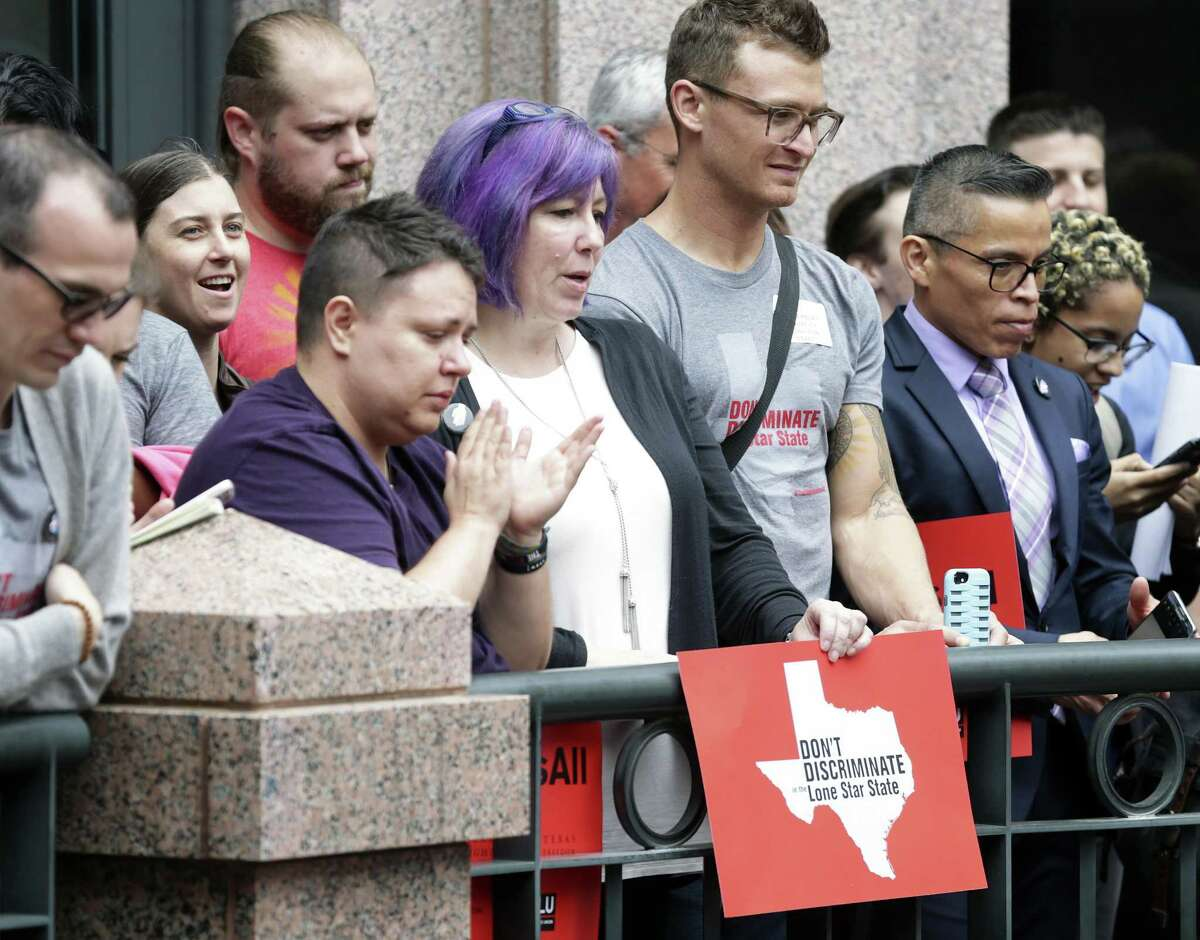 Ginger Chun (center) holds her sign in a rally in the outdoor area of the Capitol extension as the Senate State Affairs committee holds a hearing on the controversial bathroom bill,bill SB6, in the Capitol on March 7, 2017.