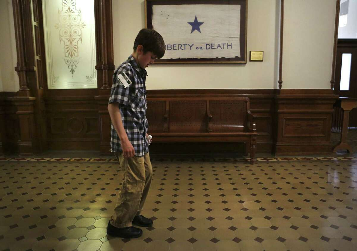Max Briggle, 9, a transgender boy from Denton, counts the tiles in the hallway outside the office of Speaker of the House Joe Straus in the State Capitol on March 6 during Trans Texas Lobby Day in Austin.