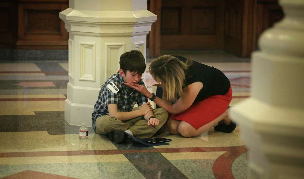 Amber Briggle, of Denton, TX, comforts her worn old and tired 9 year old transgender son Max on the floor in the State Capitol during Trans Texas Lobby Day in Austin, TX on Monday, March 6, 2017.
