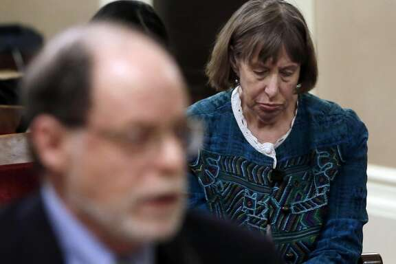 Diane Bernbaum, lowers her head as her husband, Edwin Bernbaum, left, discuses their son, Jonathan Bernbaum, a victim of last December's Oakland warehouse fire, during a hearing of the Senate Governance and Finance Committee, Wednesday, March 15, 2017, in Sacramento, Calif. Lawmakers were exploring issues related to the fire that killed 36 in a warehouse that illegally housed an artists' collective and event space. (AP Photo/Rich Pedroncelli)
