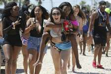 Alex Hendry, carries Unique William on their way to the beach at Clayton's Beach Bar and Grill in South Padre Island, Tuesday, March 14, 2017. Spring Break brings thousands of visitors to the island and last year, sales revenues grossed $30.5 million. Both women are students at Texas State University.