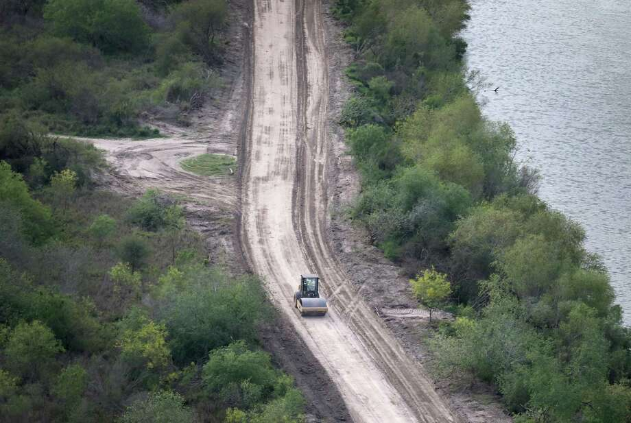 A road crew improves a road along the Rio Grande this week in Hidalgo, south of McAllen. There has been great speculation on exactly where a border wall, promised by President Trump, would be built near the Rio Grande, which forms the border between Texas and Mexico. Meanwhile, the Department of Homeland Security is moving forward on condemning property for several miles of South Texas border fence that was authorized a decade ago but never built. Photo: John Moore /Getty Images / 2017 Getty Images