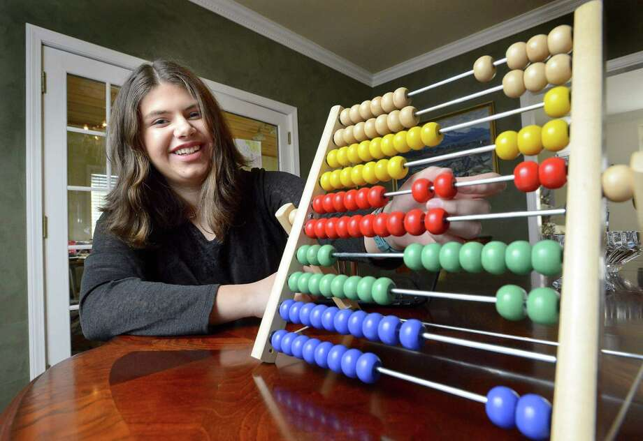 Spencer Sigtryggson, 16, at her home in Stamford with an Abacus. Sigtryggson is about to graduate from Mary Baldwin College. She left Stamford High School at the age of 14 to attend college, where she studies science and mathematics. Photo: Matthew Brown / Hearst Connecticut Media / Stamford Advocate