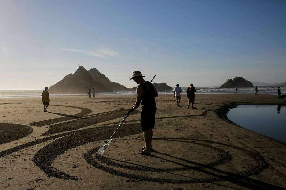 Artist Ian Ross drags a rake through the sand while making one of his artistic sand designs at Ocean Beach in San Francisco, California, on Tuesday, March 14, 2017. Photo: Gabrielle Lurie, The Chronicle