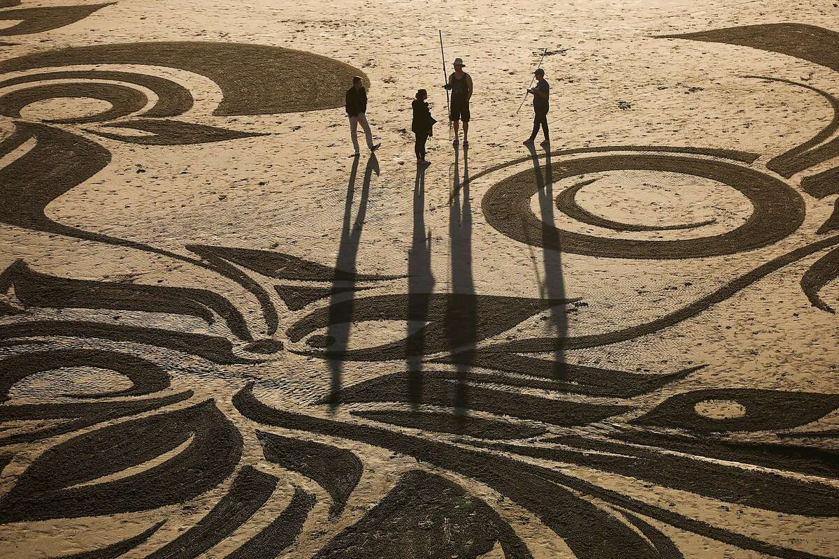 Artist Ian Ross (second from right) chats with people on the beach after making one of his artistic sand designs at Ocean Beach in San Francisco, California, on Tuesday, March 14, 2017.
