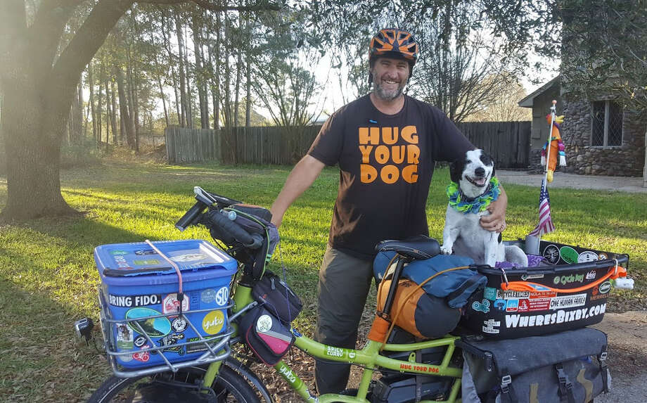 Mike Minnick and Bixby pose outside their family's home in Kingwood where they stopped for a visit Feb. 21 while on a cross-country bicycling tour to raise awareness and support for local animal shelters. Photo: Melanie Feuk