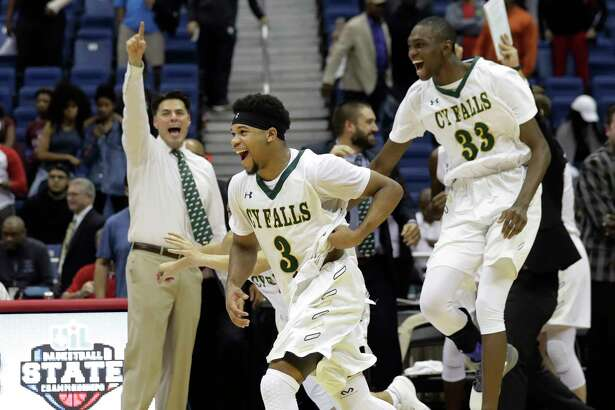 Cypress Falls coach Richard Flores, left, celebrates as he watches his players Trajan Wesley (3) and Deshang Weaver (33) run on to the court after defeating San Antonio Wagner in a UIL Class 6A boys high school state final basketball game, Saturday, March 11, 2017, in San Antonio. Cypress Falls won 63-57. (AP Photo/Eric Gay)