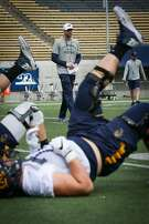 Players run drills as head coach Justin Wilcox watches at Cal football's first spring practice on Wednesday, March 14, 2017 in Berkeley, Calif.