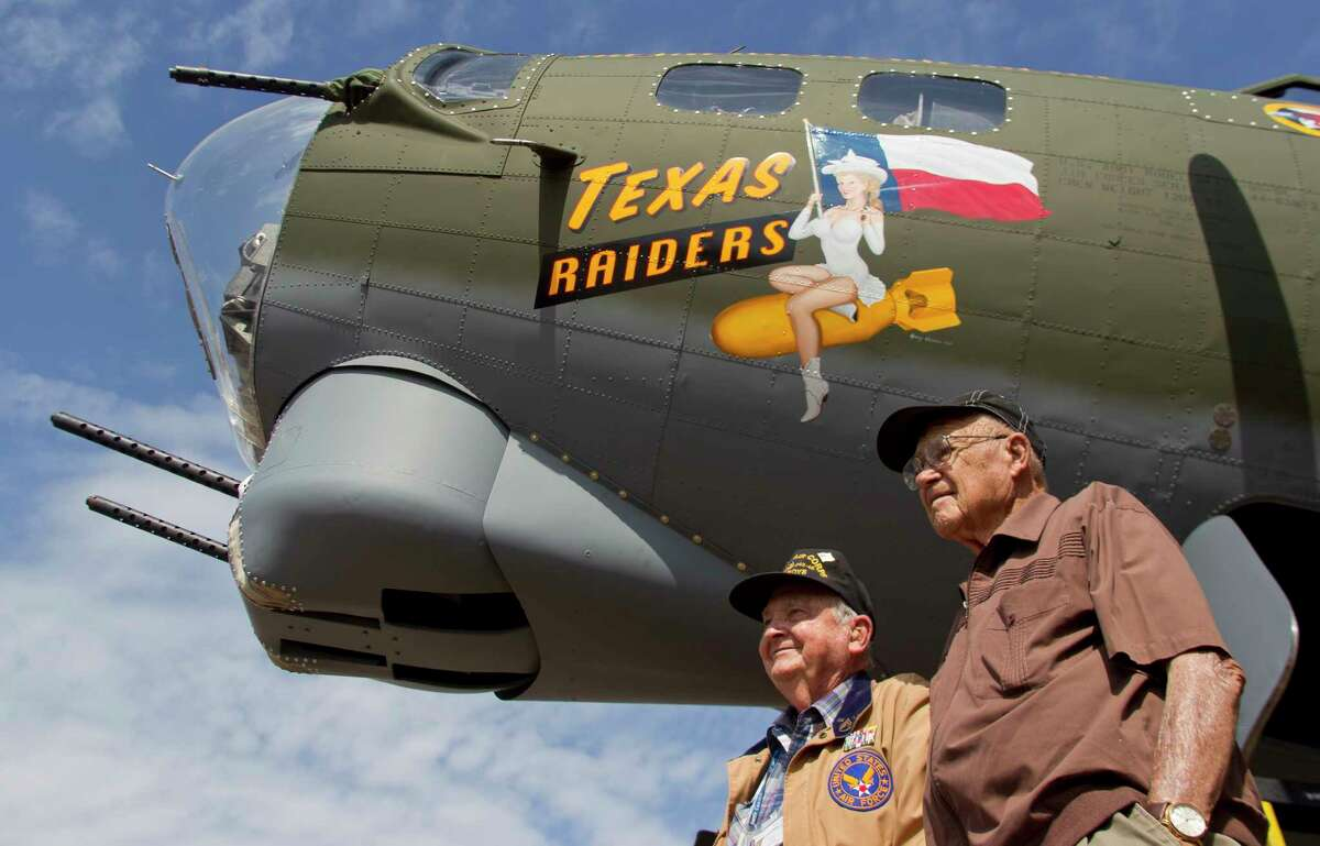 World War II veterans Curtis Blair and R.B Kelley are seen beside a B-17 Flying Fortress, known as 'Texas Raiders,' during a welcoming ceremony for the historic plane in Conroe Wednesday.