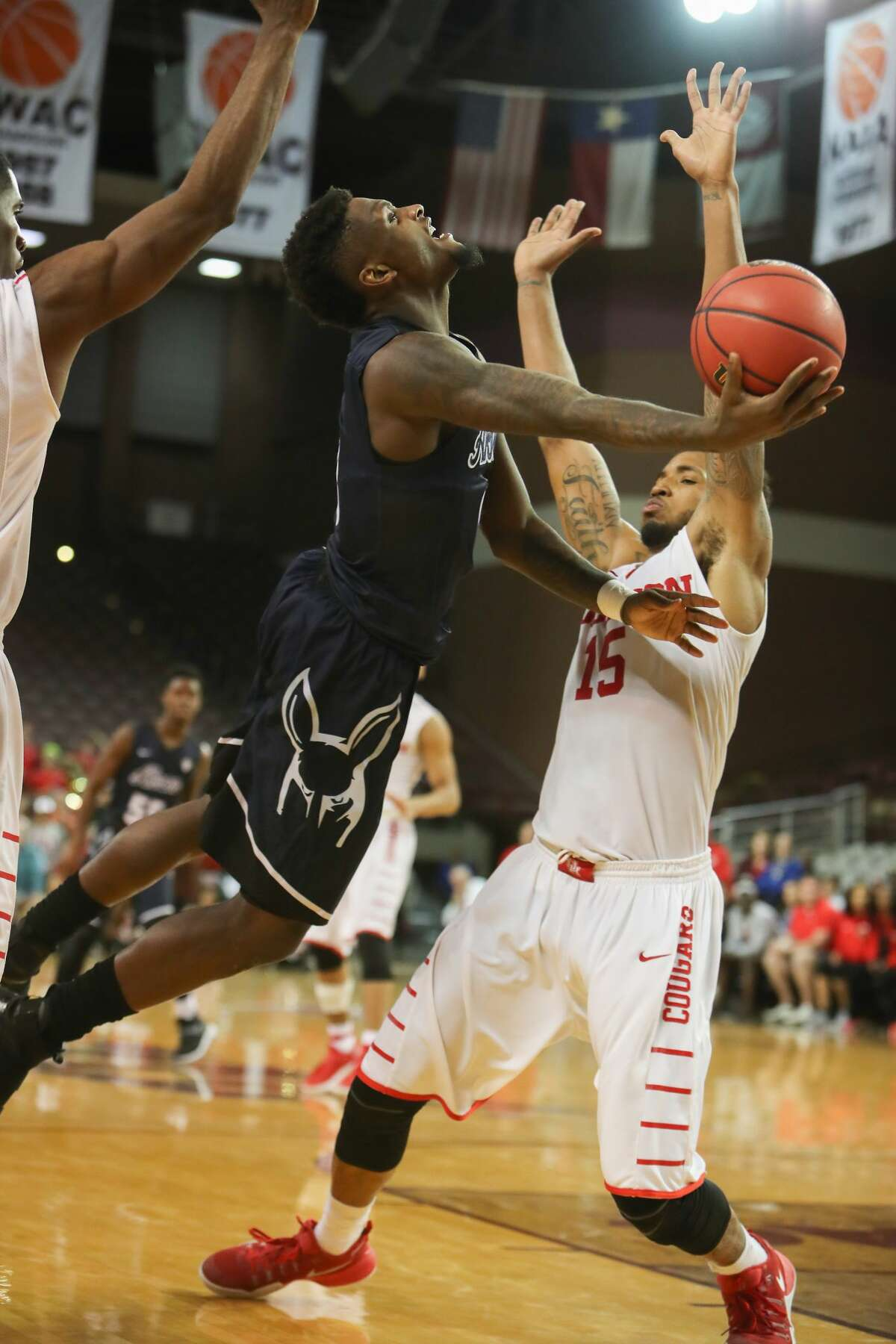 Akron Zips guard Jimond Ivey (0) shoots around Houston Cougars forward Devin Davis (15) during second half action between Houston vs. Akron in NIT basketball tournament at TSU H&PE Arena Wednesday, March 15, 2017, in Houston. ( Steve Gonzales / Houston Chronicle )