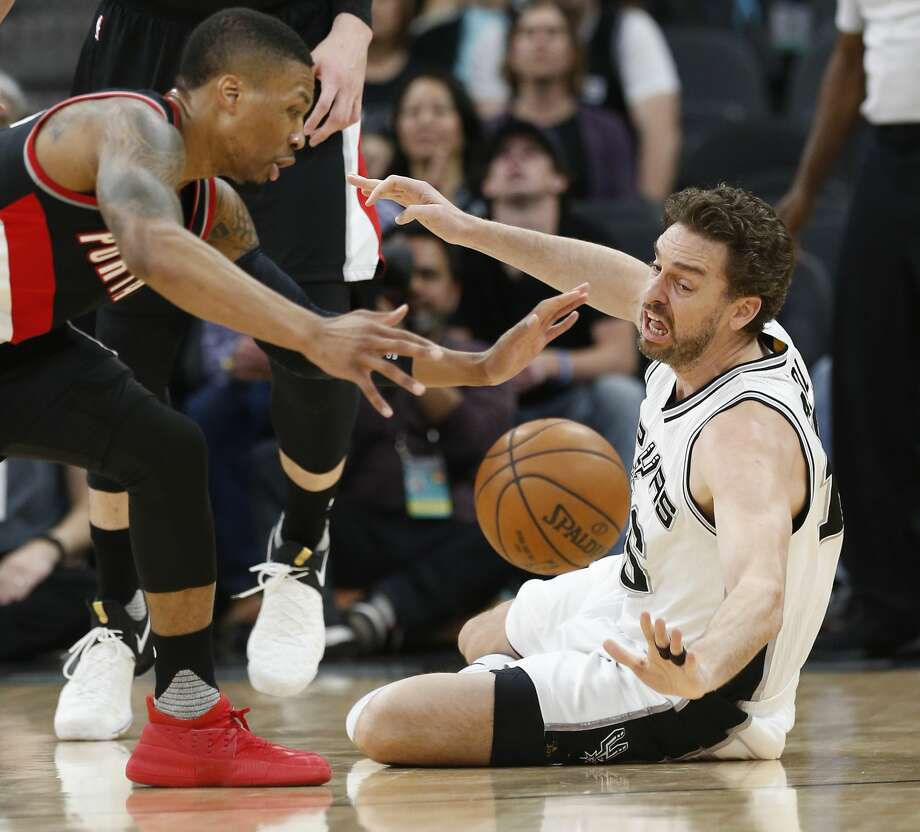Spurs' Pau Gasol (16) falls to the floor for a loose ball against Portland Trailblazers' Damian Lillard (00) during their game at the AT&T Center on Wednesday, Mar. 15, 2017. (Kin Man Hui/San Antonio Express-News) Photo: Kin Man Hui/San Antonio Express-News