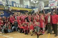 Maxwell Harden/Big Rapids Pioneer Beaverton boys' basketball coach Roy Johnston (second from right in red blazer), along with Beavers' team and fans, celebrate Wednesday's 44-31 win over Saginaw Nouvel in a Class C regional final at Morley-Stanwood.