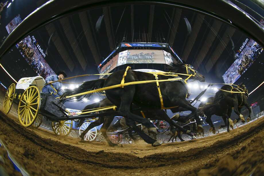 Chuckwagon racers fly by the edge of the arena during round three of Super Series III at the Houston Livestock Show and Rodeo Wednesday, March 15, 2017 in Houston. ( Michael Ciaglo / Houston Chronicle ) Photo: Michael Ciaglo/Houston Chronicle