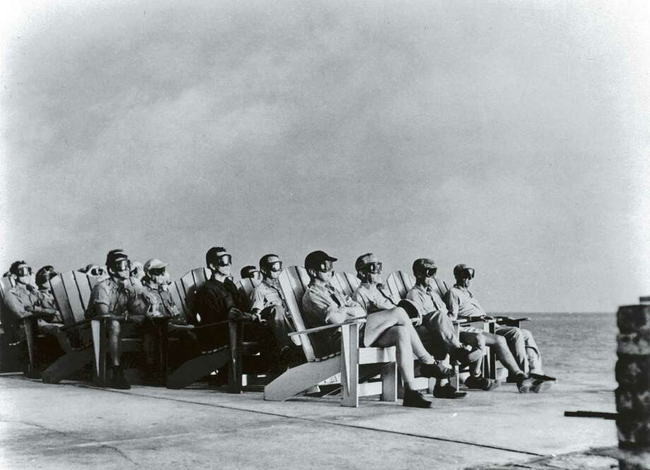 High Ranking Military Personnel Sitting In Rows Of Deck Chairs Wearing Goggles While Getting Illuminated