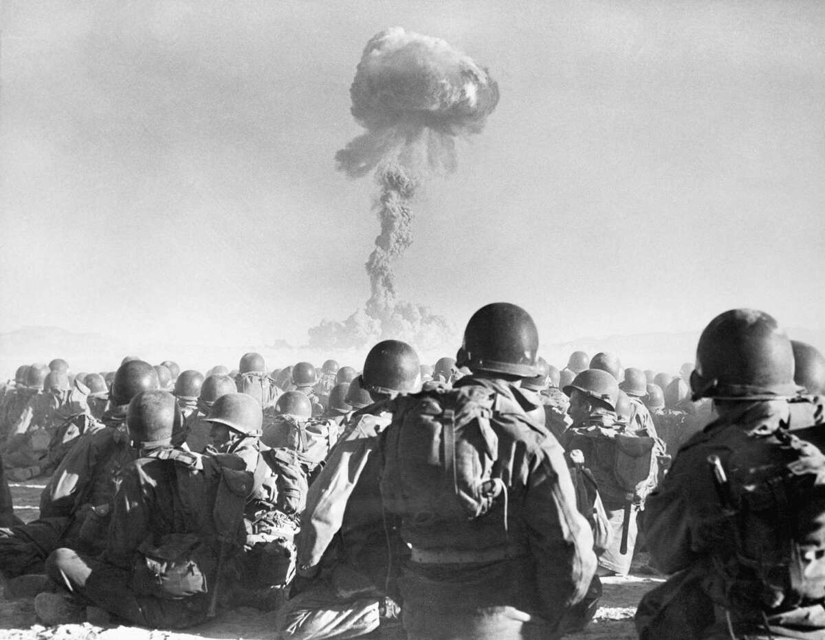"""11th Airborne division troops watch an atomic explosion at close range at the AEC's testing grounds in the Las Vegas desert. The troops participate in the """"Buster Dog"""" exercise on November 1, 1951, during Operation Buster-Jangle. This is the first time troops have been employed in maneuvers where an atomic weapon was used."""
