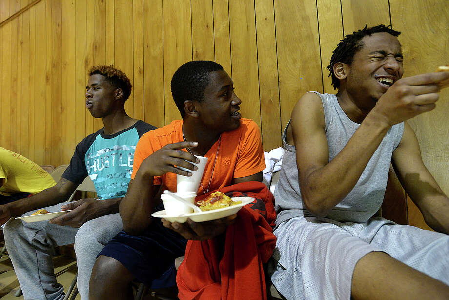 Jamaine Eaglin (far right) cracks up as he and friends joke during a lunch break from basketball while spending the day at the YYAFA Center gymnasium on the grounds at Solid Rock Community Church Wednesday. The open gym time is among the activities offered by the program during spring break. The recreation and food service program sees an increase in participation in the daily events, which includes a meal, as many area children miss out on the food programs offered daily at school when they are on break. Photo taken Wednesday, March 15, 2017 Kim Brent/The Enterprise Photo: Kim Brent, Beaumont Enterprise / BEN