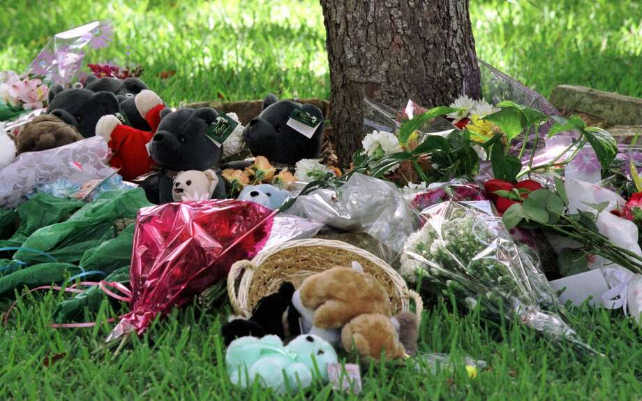 Flowers and teddy bears left behind by friends and neighbors lie June 21, 2001 in front of the Yates home. Photo: Getty Images