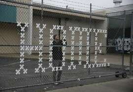 """Artist Brian Singer fixes his art installation, """"Home Street Home"""", which was intended to bring attention to the issue of homelessness and the need for affordable housing solutions,��on a fence at 1990 Folsom Street in the Mission on Wednesday, March 15, 2017 in San Francisco, Calif. The property is slated for development of 143 affordable housing units."""